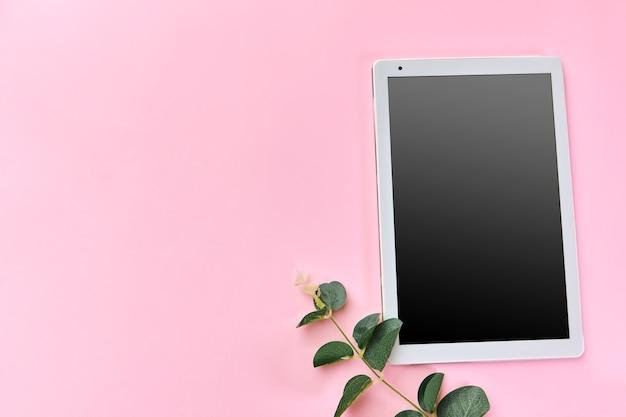 빈 태블릿 및 잎 분홍색 표면에 작업 공간