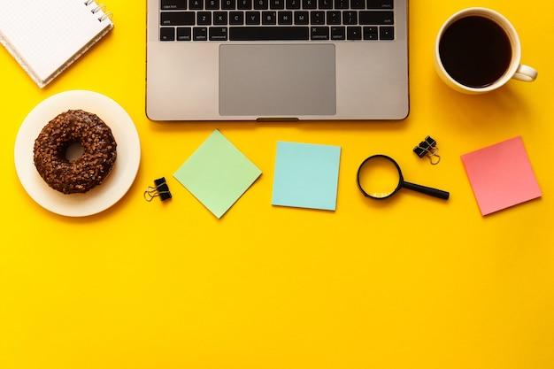ノートパソコン、コーヒー、付箋、ドーナツのある作業スペース