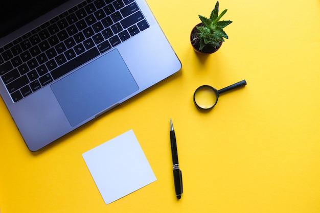 黄色の表面にラップトップ、ペン、空白のシートを備えた作業スペース