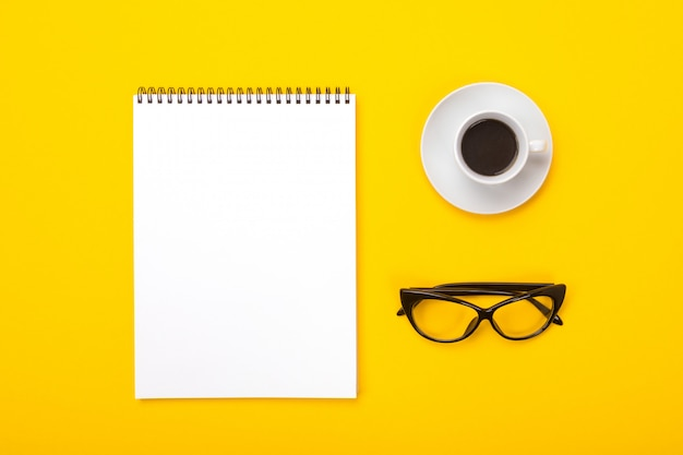 Working space with notebook, glasses and cup of coffee in morning isolated on yellow background