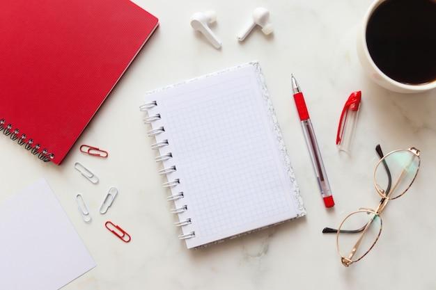 コピースペースと大理石の背景に赤いノート、女性のメガネ、一杯のコーヒーとペーパークリップの作業スペース。フレーム。事業コンセプト