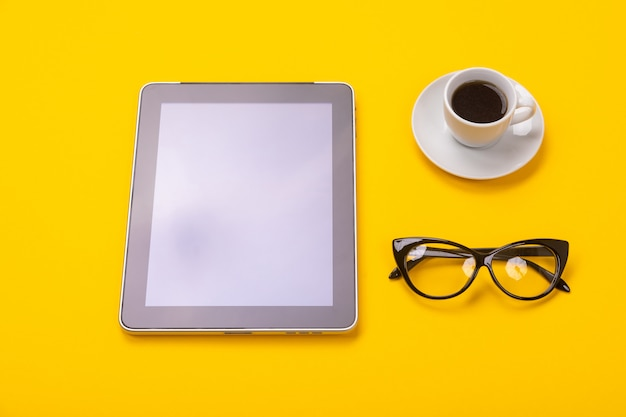 Working space with tablet, glasses and cup of coffee in morning isolated on yellow background
