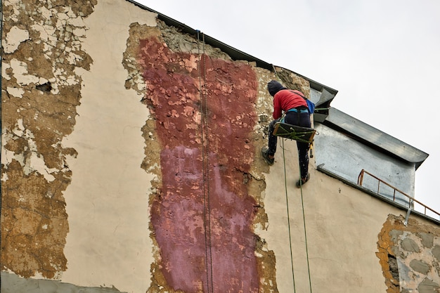 Working steeplejack with special equipment repairs the facade of the building