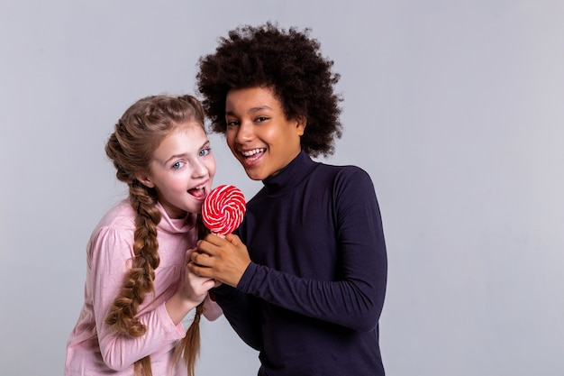 Working on studio. beaming light-haired girl with big blue eyes licking red candy while her friend holding it