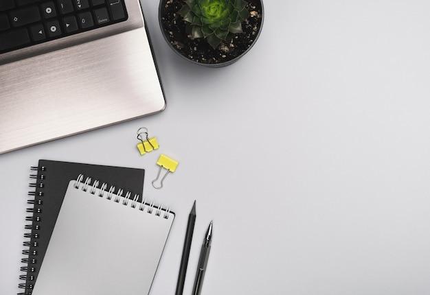 作業台、ホームオフィス。ノートパソコン、メモ帳、灰色の机の上のペン