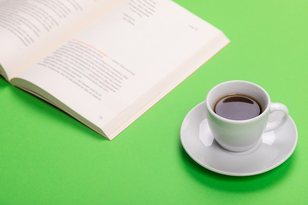 Working table with cup of coffee and book isolated on green tshirt