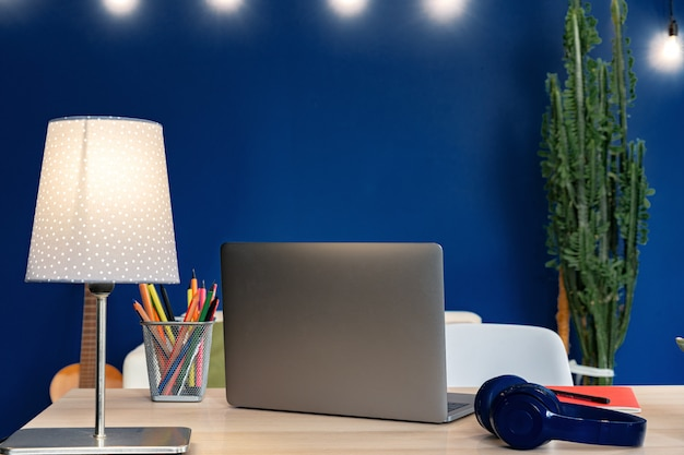 Working table with laptop against blue wall in modern flat