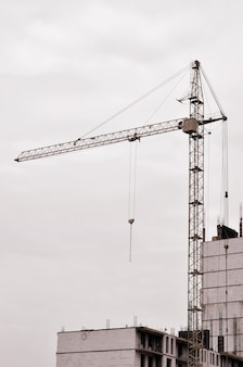 Working tall cranes inside place for with tall buildings under