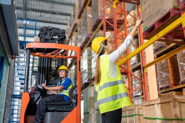 지게차 로더가 있는 창고의 보관 부서에 추가 배치에 대한 정보를 확인하고 관리자가 노란색 헬멧으로 안전 작업복을 가리키는 창고.아시아 여성 작업자의 작업 팀