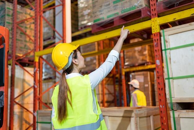 창고에서 작업 팀입니다. 노란색 헬멧을 쓰고 안전 작업복을 입고 일하는 아시아 여성 근로자와 관리자는 대형 창고의 보관 부서에 추가 배치에 대한 정보를 확인합니다.