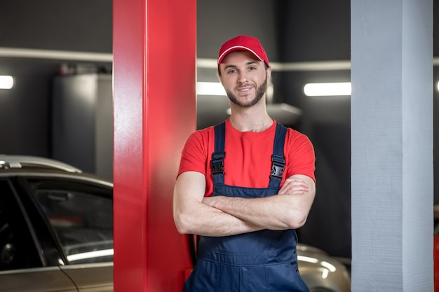 労働時間。仕事のオーバーオールと自動車のワークショップで立っているキャップで若いひげを生やした男の笑顔