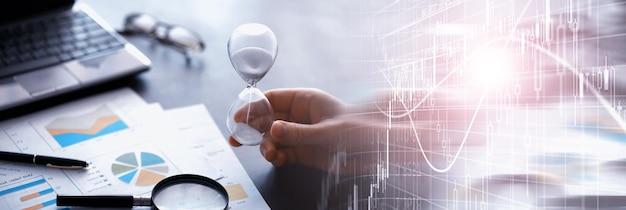 Время работы символизирует песочные часы. офисный стол со страховым менеджером и банкиром. офисный работник за столом. понятие нехватки времени.