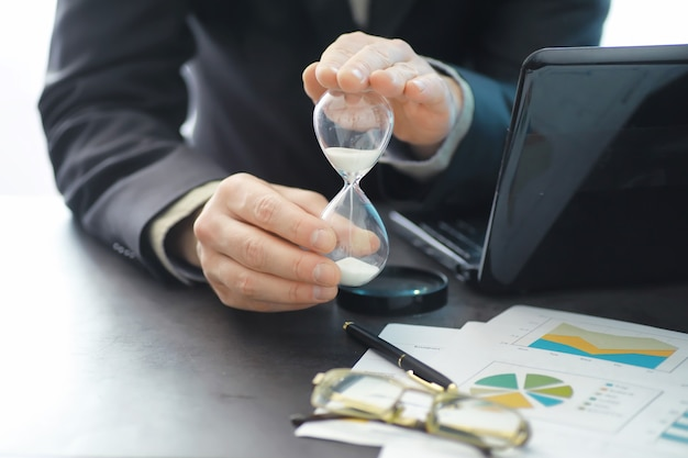 Working time symbolizes an hourglass. office desk with insurance manager and banker. office employee at the table. the concept of lack of time.