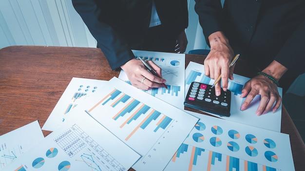 データと管理を計算するための計算機を備えた財務チャートとグラフでビジネスウーマンと協力する。