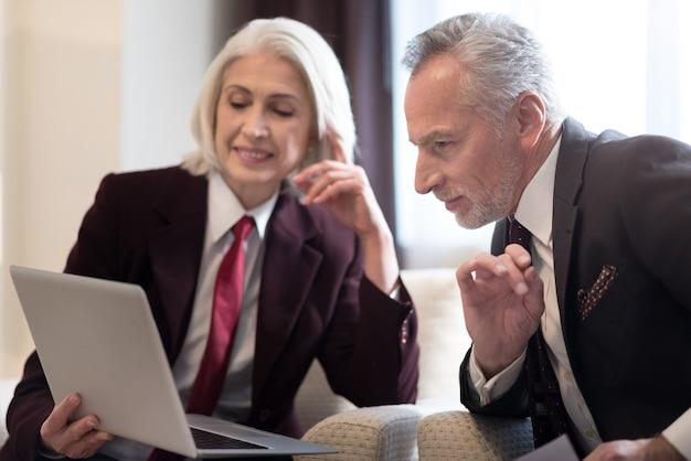 一緒に働いている。ノートパソコンを見て、同僚とプロジェクトについて話し合い、ノートパソコンを持ってオフィスに座っている陽気な笑顔の高齢の実業家