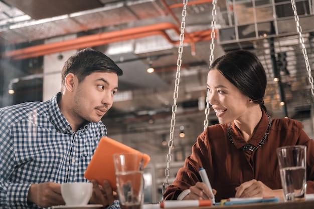 一緒に働いている。一緒に働いている間気分が良い賢い有望なビジネスマンのカップル