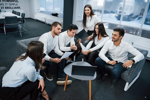 Работаем вместе в дружеской обстановке возле стола с серебристым ноутбуком