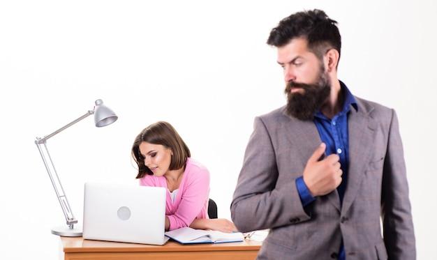 一緒に働いている。マネージャーのボスはラップトップで忙しい女の子の前に立っています。オフィスマネージャーまたは秘書。セクシーな女性サラリーマン。個人秘書。典型的なオフィスライフ。オフィスの集合的な概念。