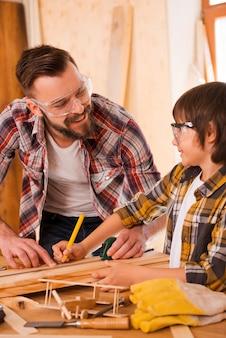 一緒に働いている。ワークショップで働いている間お互いを見ている若い男性の大工と彼の息子の笑顔