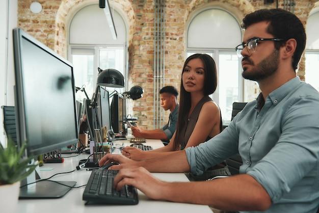 Работая вместе, два молодых деловых человека работают на компьютерах и обсуждают новый проект, пока