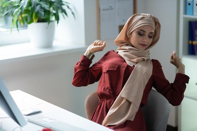 働きすぎです。コンピューターで長時間作業した後、背中を伸ばすイスラム教徒の女性