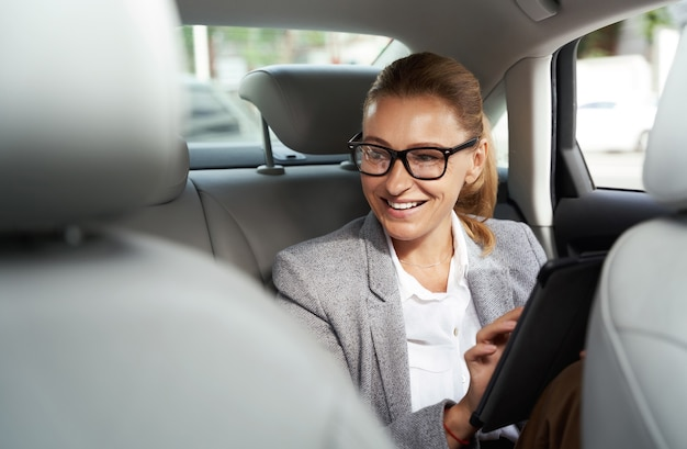 Working on the way to the office successful business woman wearing eyeglasses using digital tablet
