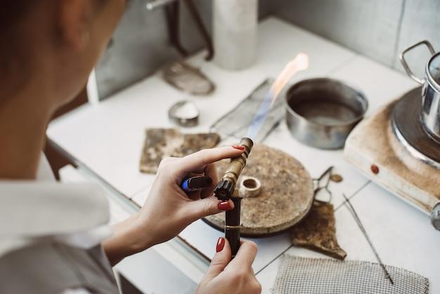 불 작업. 그녀의 보석 제작 워크샵에서 여성 보석상이 은반지를 납땜하고 용접합니다. 사업. 보석 장비. 부속품