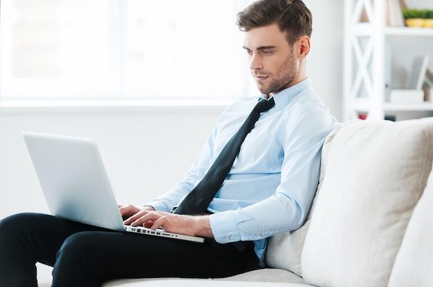 Комфортная работа. серьезный молодой бизнесмен, работающий на ноутбуке, сидя на диване