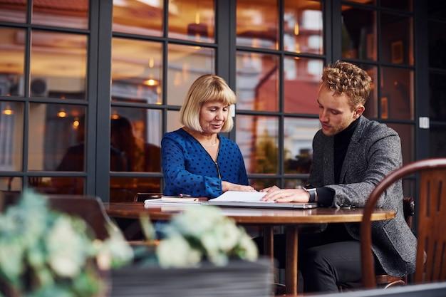 ドキュメントの操作。正装の若い男がカフェで老婆と商談。