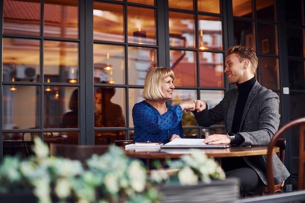 문서 작업. 정장 차림의 젊은 남자가 카페에서 노파와 비즈니스 이야기를 나눴다.