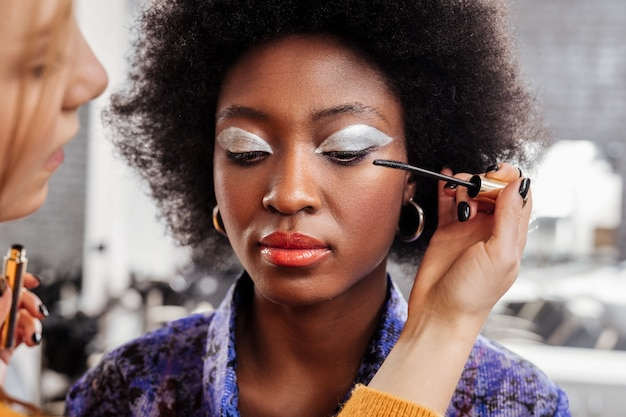 Working with eye makeup. fair-haired young stylist wearing black nail polish doing makeup to a model