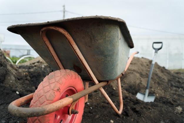 Работа с садовыми инструментами лопатой и тачкой на участке подготовки загородного дома к