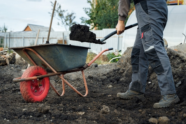 Working with garden tools shovel and wheelbarrow on the site of a country house preparation for