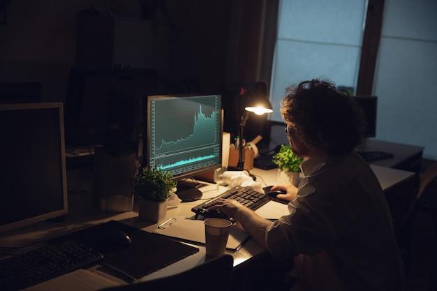 Работа с графиками. человек, работающий в офисе, до поздней ночи.