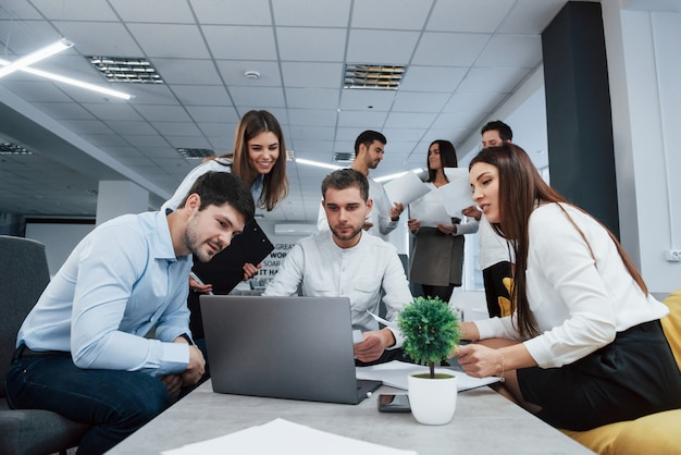 노트북으로 작업. 사무실에서 젊은 프리랜서 그룹 대화 및 미소