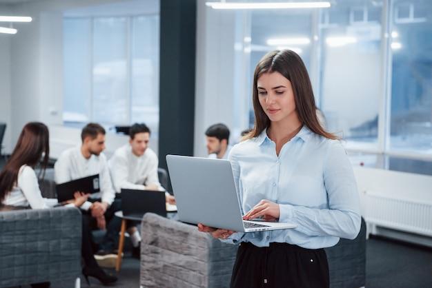 ラップトップでの作業。バックグラウンドで従業員とオフィスに立っている若い女の子の肖像画
