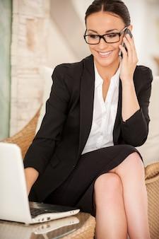Работаем с удовольствием. веселая молодая женщина в строгой одежде работает на ноутбуке и разговаривает по мобильному телефону, сидя в удобном кресле