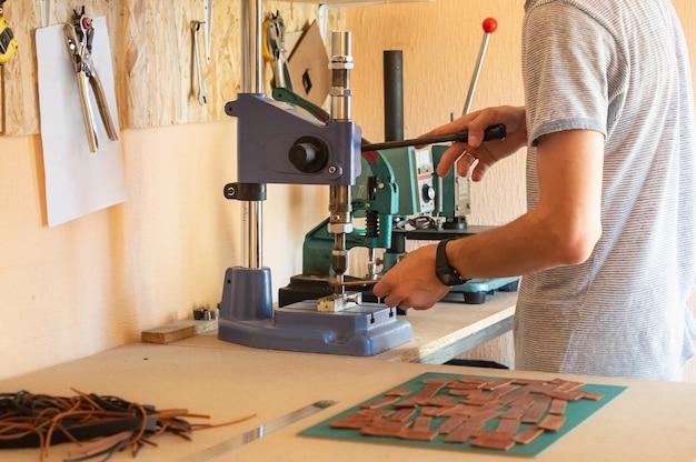 Работа с пресс-машиной в небольшой мастерской по изготовлению кожаных изделий. мужские руки с помощью зажимного устройства для установки заклепок на кусочки кожи