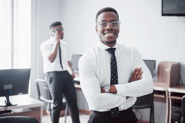 笑顔で働きます。同僚の前に立っている陽気なアフリカの実業家。