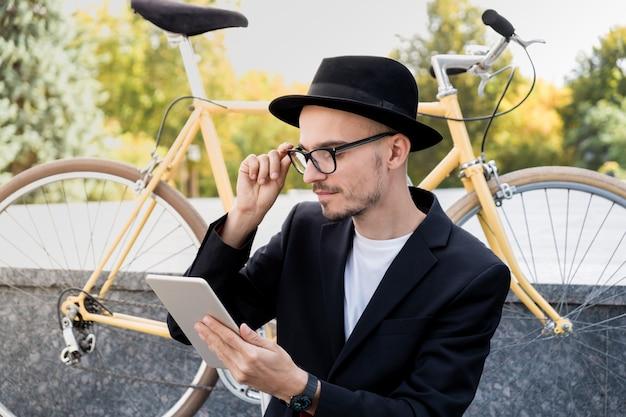 不在の概念の技術を使用しています。市街地でタブレットコンピューターを使用してカジュアルなスーツを着た若い男の肖像