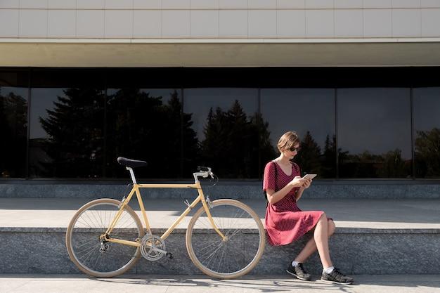不在時のテクノロジーの使用。通勤用自転車の隣に座って、市街地で屋外にタブレットコンピューターを使用してスタイリッシュなレトロなドレスの若い女性