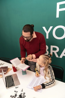 Работа с книгой темноволосый бородатый взрослый учитель в очках выглядит занятым, работая со своим учеником