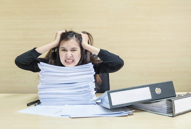 Working woman are stressed from work paper and document file in front of her