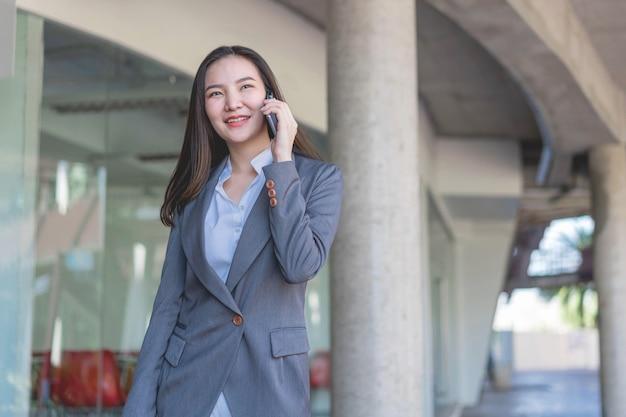 働く女性のコンセプトは、オフィスの外でのビジネスについて顧客に電話をかける実業家です。
