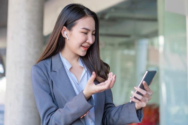 働く女性のコンセプトは、オフィスの外で顧客とビデオ会議をしている実業家です。