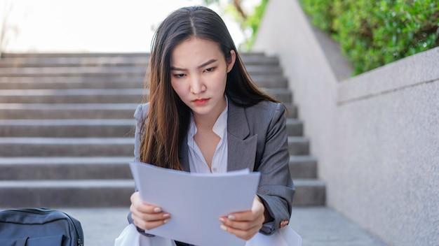 働く女性のコンセプト不安と絶望を感じながら求人応募を見ている階段に座っている女性。