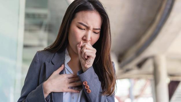 働く女性のコンセプト何の保護もなく働いている間に多くの人々と接触した後に咳をする働く女性。