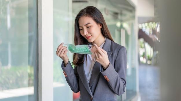 일하는 여성은 코로나 바이러스로부터 자신을 보호하기 위해 일회용 안면 마스크를 착용하여 고객을 만나기 전에 자신을 준비하는 일하는 여성을 컨셉으로 합니다.