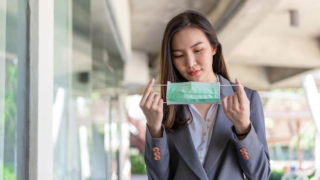 働く女性のコンセプトコロナウイルスから身を守るために使い捨てのフェイスマスクを着用して、クライアントに会う前に自分自身を準備する働く女性。