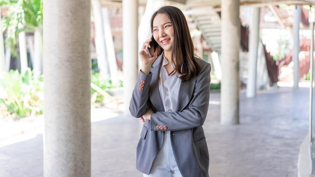 働く女性の概念彼女のビジネスパートナーと電話で話すスマイリーフェイスを持つ働く女性。
